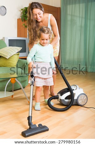 Happy mother and daughter chores with vacuum cleaner in home
