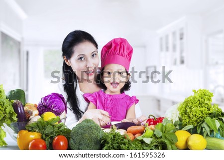 Happy mother and daughter cooking vegetable salad together - stock photo