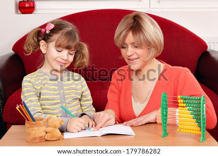 happy mother and daughter doing homework - stock photo