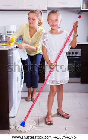 Happy mother and daughter doing regular cleanup together at kitchen. Focus on girl