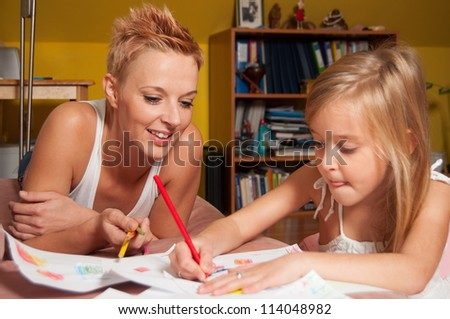 Happy mother and daughter drawing at their home. - stock photo