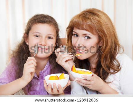 Happy mother and daughter eating cereal and fruit - stock photo