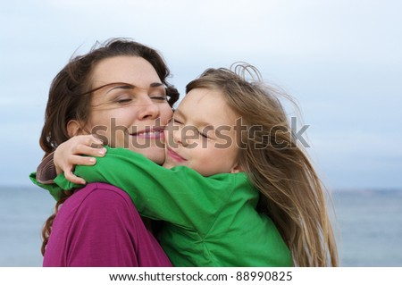 Happy mother and daughter embracing at beach. - stock photo
