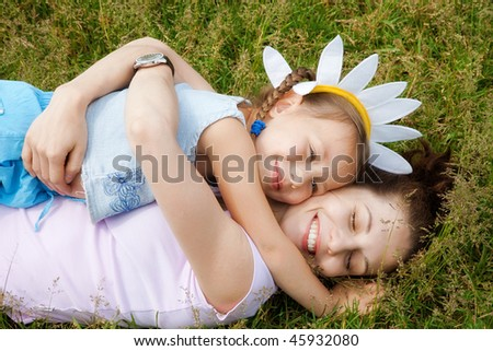 Happy mother and daughter embracing on the grass - stock photo
