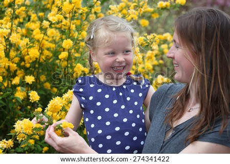 Happy mother and daughter enjoy the flowers in the garden - stock photo