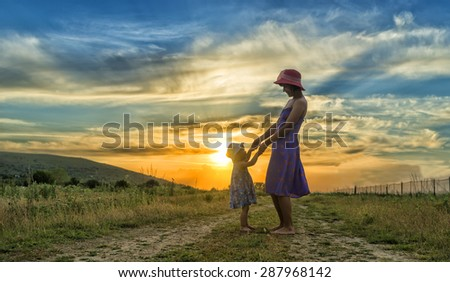 happy mother and daughter having fun at sunset - stock photo