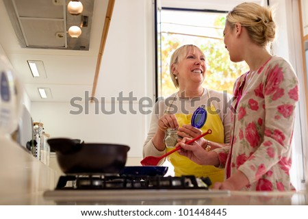 Happy mother and daughter having fun while preparing food and cooking together in kitchen at home