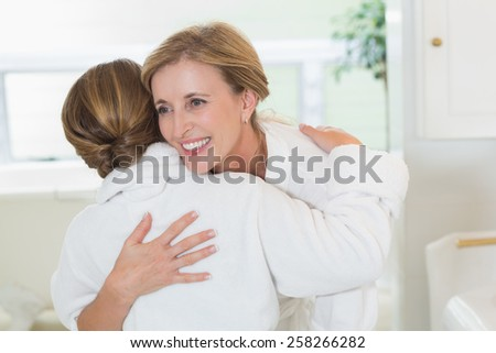 Happy mother and daughter hugging in the bathroom - stock photo