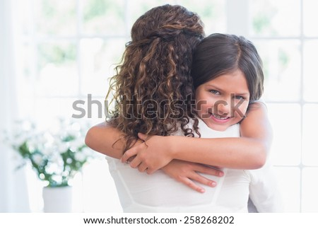 Happy mother and daughter hugging in the living room - stock photo