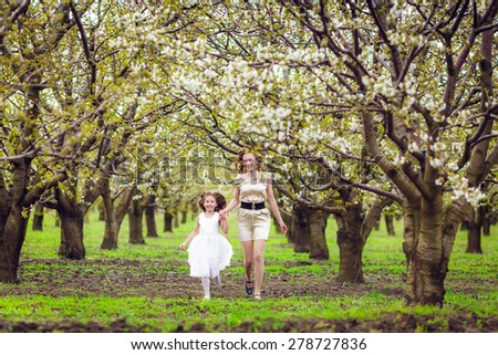 Happy mother and daughter in the flowered garden