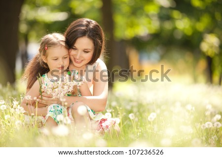 Happy mother and daughter in the park. Beauty nature scene with family outdoor lifestyle. Happy family resting together on the green grass, having fun outdoor. Happiness and harmony in family life.