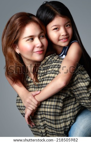Happy mother and daughter, Isolated on grey background - stock photo