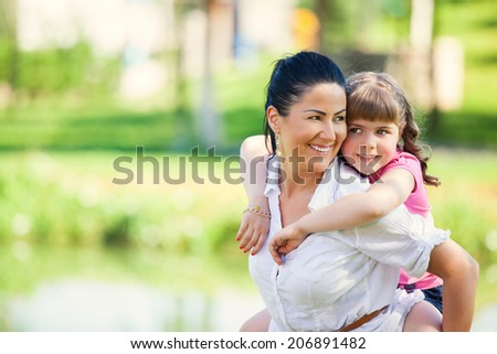 Happy mother and daughter laughing together outdoors - stock photo