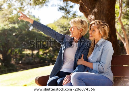 happy mother and daughter looking and pointing in the park - stock photo