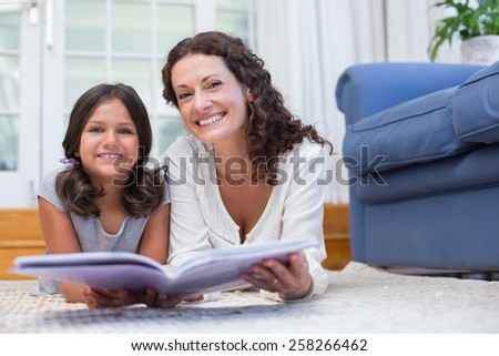Happy mother and daughter lying on the floor and reading a book in the living room - stock photo