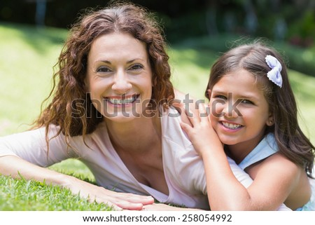Happy mother and daughter lying on the grass in the garden - stock photo