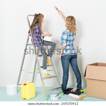 Happy mother and daughter makes repairs at home. - stock photo