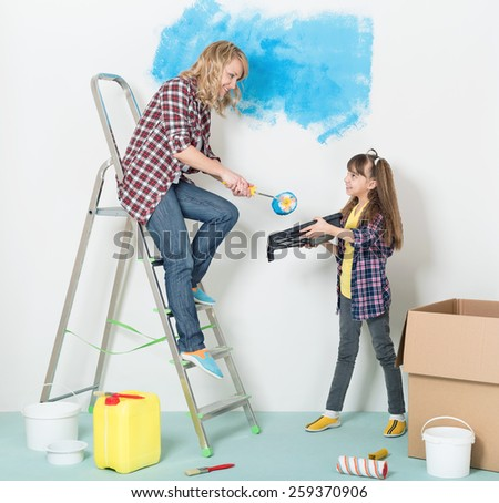 Happy mother and daughter makes repairs at home - painting wall at room.