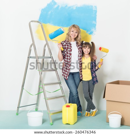 Happy mother and daughter makes repairs at home. Smiling woman and girl painting big Ukrainian flag on wall at room.