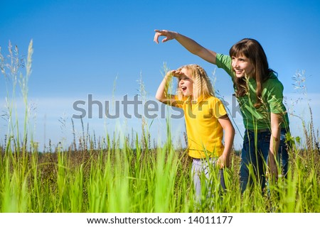 Happy Mother and Daughter on Field. Girl Surprised Something. - stock photo