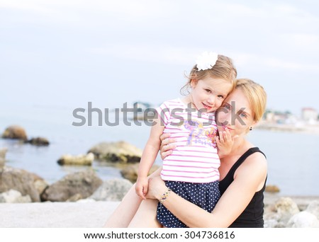 Happy mother and daughter on the beach  - stock photo