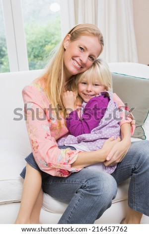 Happy mother and daughter on the couch at home in the living room