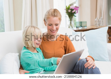 Happy mother and daughter on the couch using laptop at home in the living room