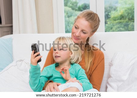 Happy mother and daughter on the couch using smartphone at home in the living room - stock photo