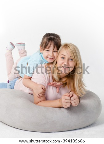 Happy mother and daughter on the cushion  - isolated over a white background