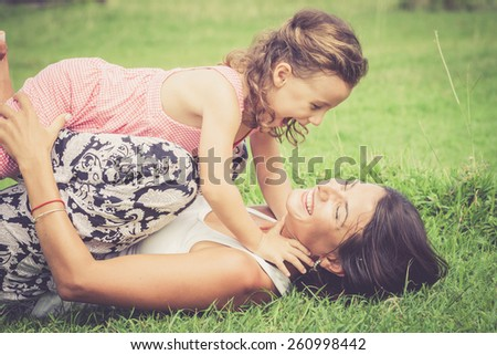 Happy mother and daughter playing in the park at the day time. Concept of celebration Mothers day . - stock photo