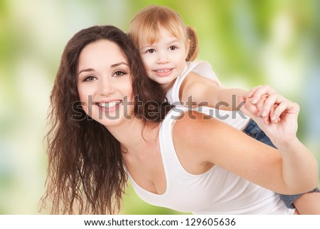 Happy mother and daughter playing on nature background - stock photo
