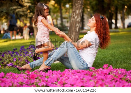 Happy mother and daughter playing on the green grass in the park.