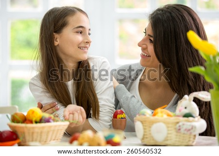Happy mother and daughter preparing Easter eggs together - stock photo