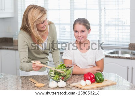 Happy mother and daughter preparing salad together at home in the kitchen - stock photo