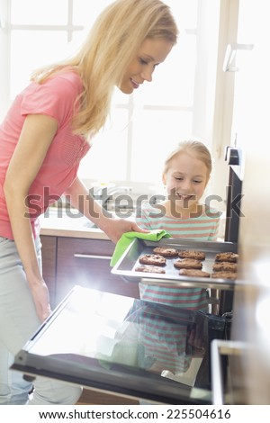 Happy mother and daughter removing cookie tray from oven at home - stock photo