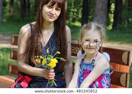 Happy mother and daughter sit with flowers on bench in park at summer, focus on child