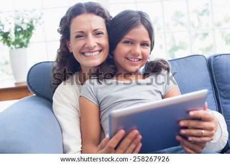 Happy mother and daughter sitting on the couch and using tablet in the living room - stock photo