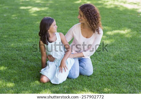 Happy mother and daughter sitting on the grass in the garden