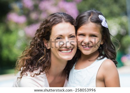 Happy mother and daughter smiling at camera in the garden - stock photo