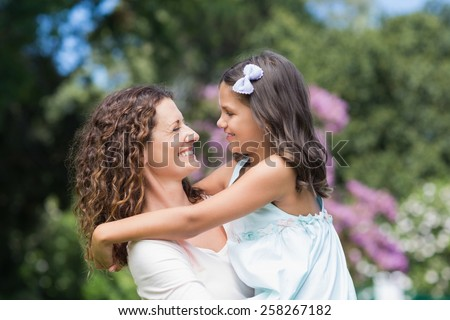 Happy mother and daughter smiling at each other in the garden - stock photo