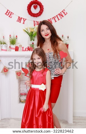 Happy mother and daughter spending time together over charming interior on Holiday theme - stock photo