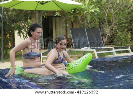 Happy mother and daughter swimming in the pool on an inflatable  crocodile - stock photo