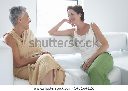 Happy mother and daughter talking on sofa in living room - stock photo