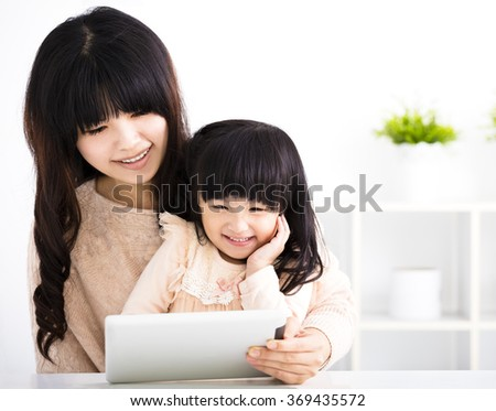 happy mother and daughter using digital tablet in the living room - stock photo