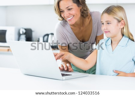Happy mother and daughter using laptop in the kitchen - stock photo