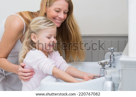Happy mother and daughter washing hands at home in the bathroom - stock photo
