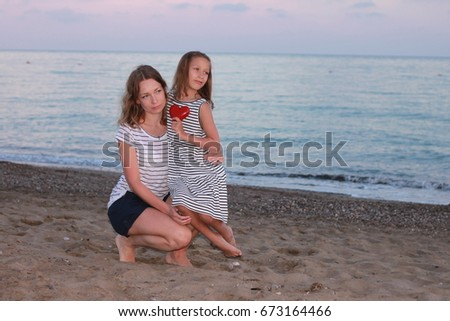 Happy mother and daughter with a heart in hands on the beach at sunset time. Summer holidays, travel, vacation concept.