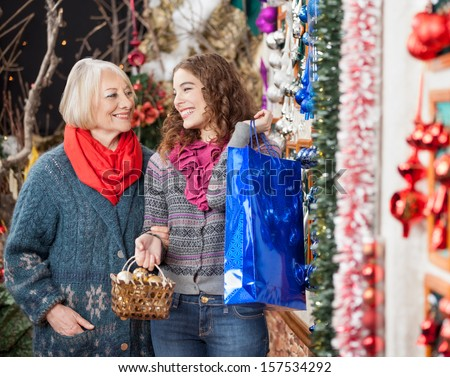 Happy mother and daughter with bags shopping in Christmas store