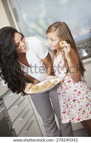 Happy mother and daughter with cookies - stock photo