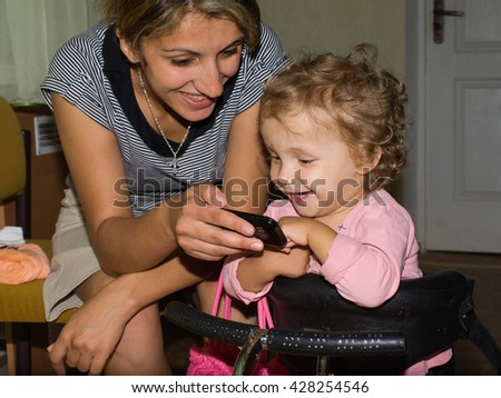 Happy mother and daughter with mobile phone - stock photo